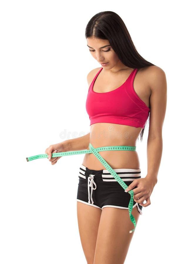Härlig ung flicka som kontrollerar henne waistline arkivbild