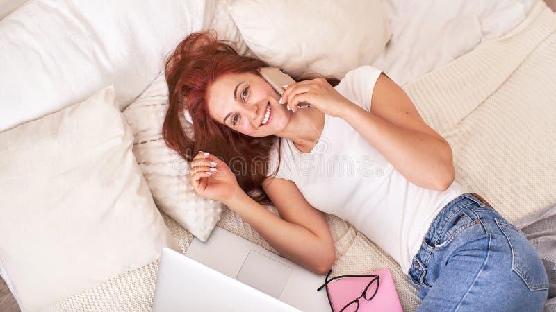 Härlig ung flicka som ler med telefonen och bärbara datorn på sängen royaltyfri bild