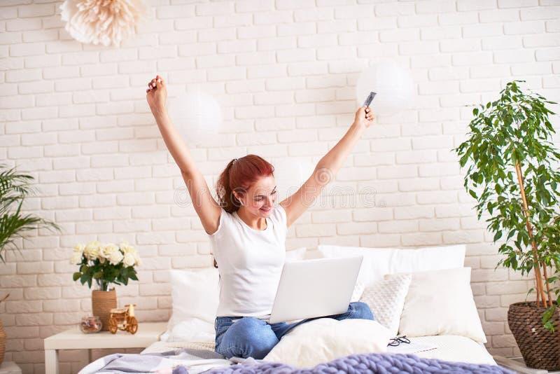 Härlig ung flicka som ler och rymmer en kontokort och en bärbar dator på sängen royaltyfri fotografi