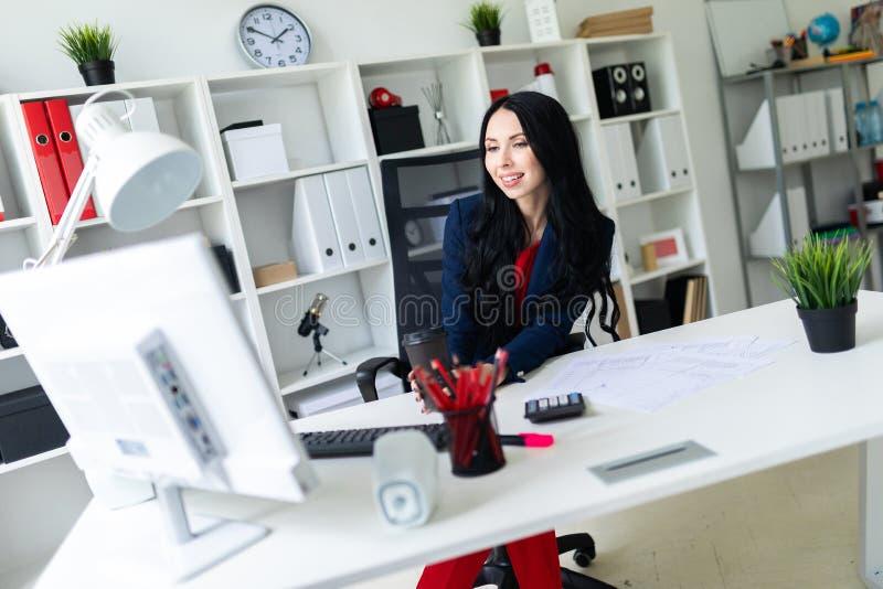 Härlig ung flicka som rymmer ett exponeringsglas med kaffe och ser bildskärmen som sitter på en stol i kontoret på arkivfoton