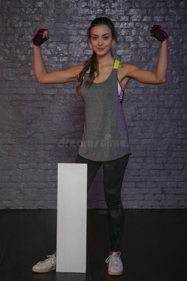 Härlig ung flicka som rymmer ett tomt bräde, kopieringsutrymme för annonsering, muskler och idrottshallen, begreppsmässigt foto s royaltyfri fotografi