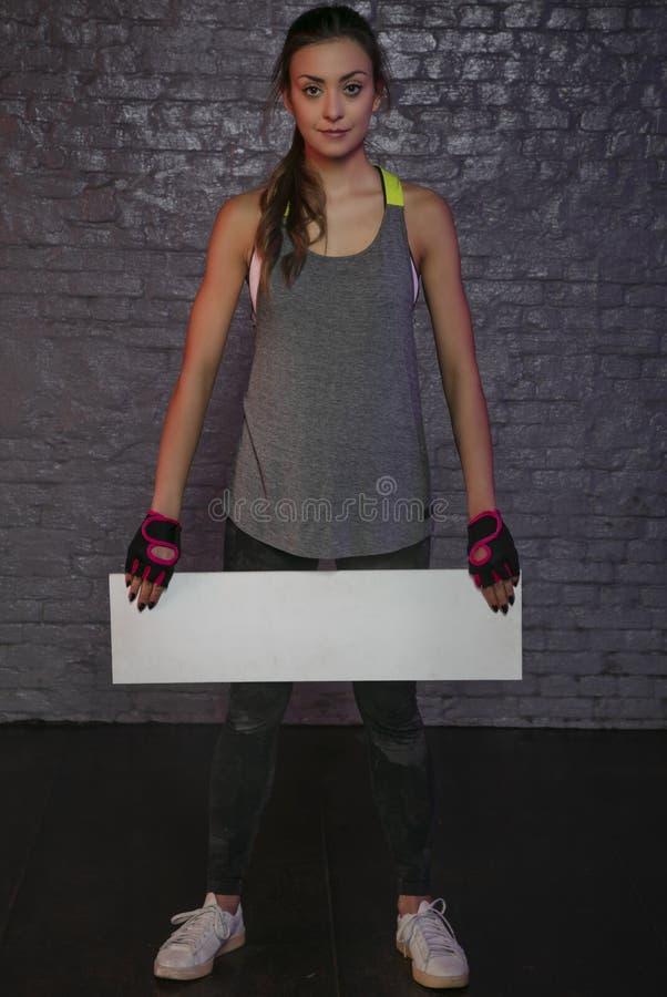 Härlig ung flicka som rymmer ett tomt bräde, kopieringsutrymme för annonsering, muskler och idrottshallen, begreppsmässigt foto s royaltyfri bild