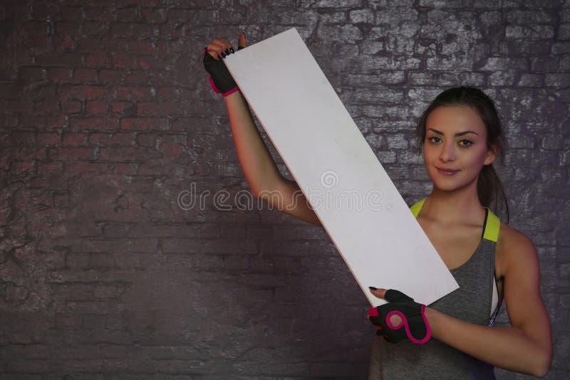 Härlig ung flicka som rymmer ett tomt bräde, kopieringsutrymme för annonsering, muskler och idrottshallen, begreppsmässigt foto s royaltyfria foton