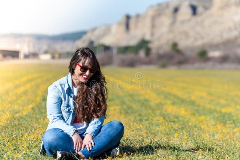 Härlig ung flicka som sitter på det utomhus- gräset fotografering för bildbyråer