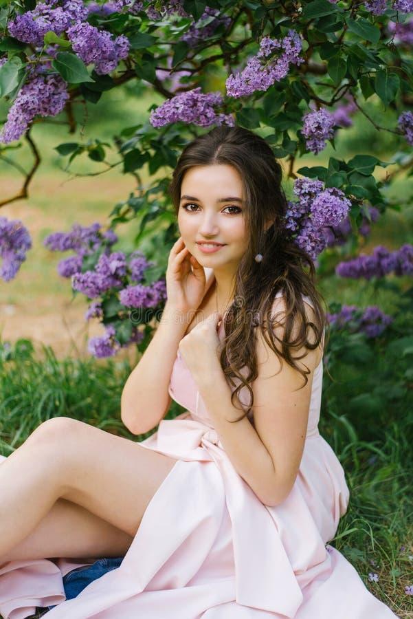 Härlig ung flicka som sitter på jordningen i trädgården med att blomma lilan Hon är lycklig och tycker om hennes ungdom och vår P royaltyfri bild