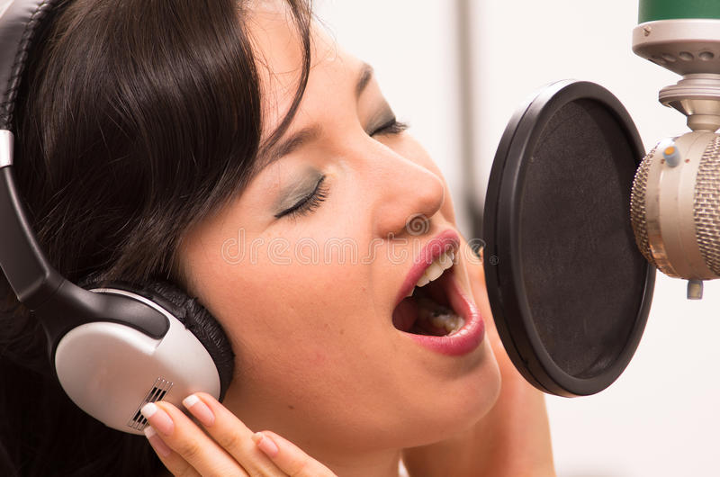 Härlig ung flicka som sjunger i musikstudio arkivbilder