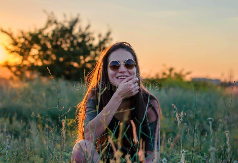 Härlig ung flicka som skrattar i rund solglasögon i solnedgångljuset royaltyfri foto