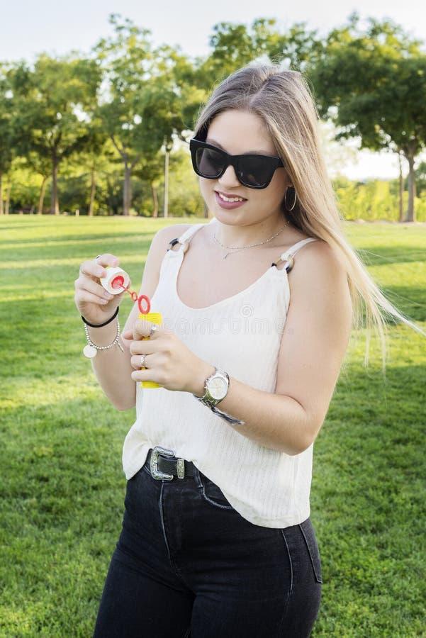 Härlig ung flicka som spelar med en bubblablåsare arkivfoton
