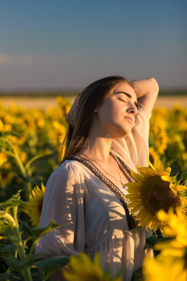 Härlig ung flicka som tycker om naturen på fältet av solrosor royaltyfri fotografi