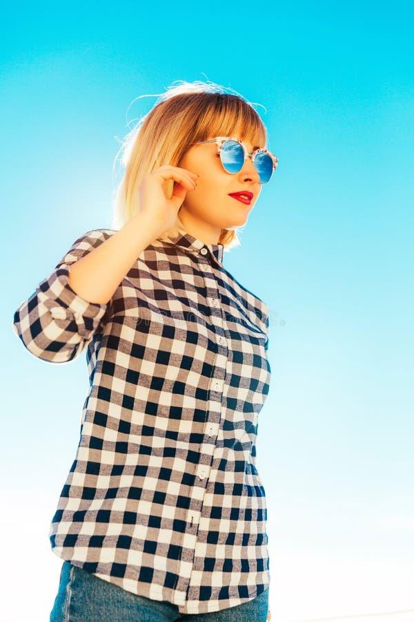 Härlig ung flickablondin med röda kanter i exponeringsglas och en plädskjorta på havet livsstil swallowtail för sommar för fjäril royaltyfria bilder