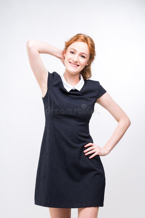 H?rlig ung flickastudent, sekreterare eller aff?rsdam med att charma leende och r?tt lockigt h?r i svart kl?nning i vit arkivfoto