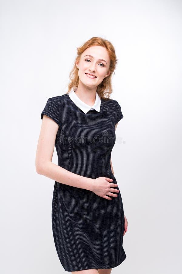 Härlig ung flickastudent, sekreterare eller affärsdam med charmigt leende och rött lockigt hår i svart klänning i den vit pricken arkivfoto