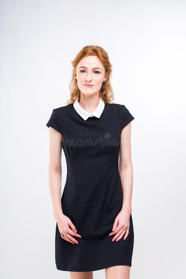 Härlig ung flickastudent, sekreterare eller affärsdam med charmigt leende och rött lockigt hår i svart klänning i den vit pricken arkivbild