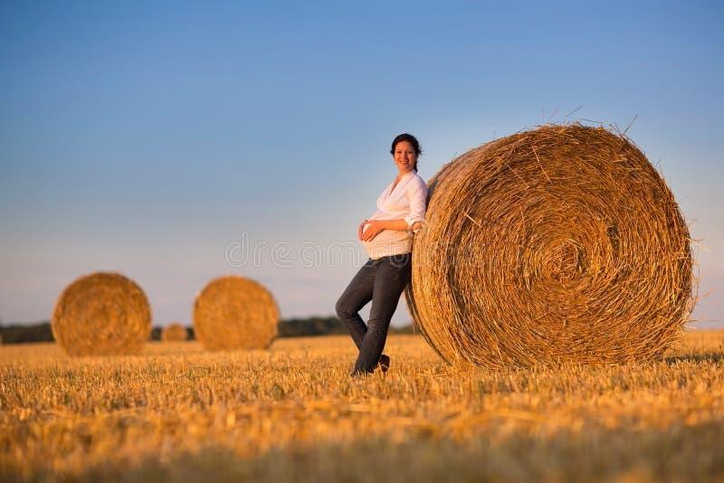 Härlig ung gravid kvinna som kopplar av i ett fält för höbaler royaltyfri foto