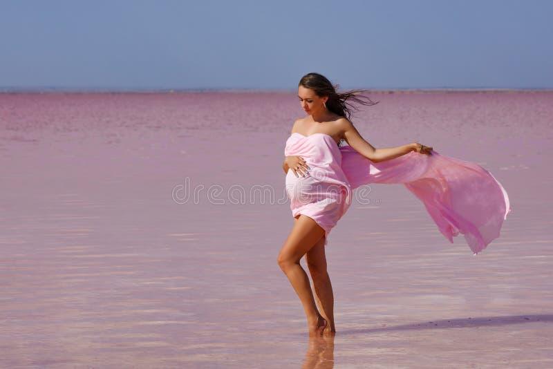 Härlig ung gravid kvinna som tycker om solen på stranden, rosa sjö royaltyfri bild