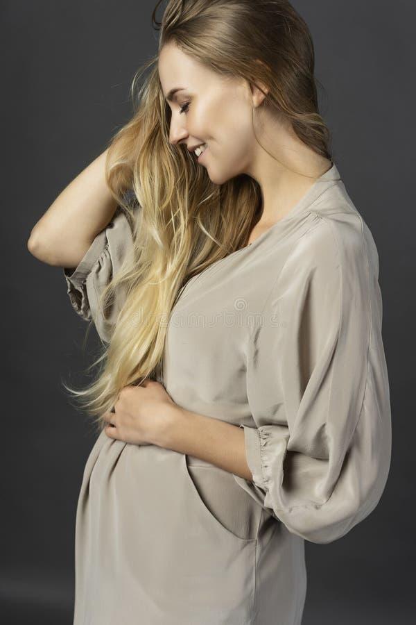 Härlig ung gravid kvinnablondin som bär en kort ljus gra fotografering för bildbyråer