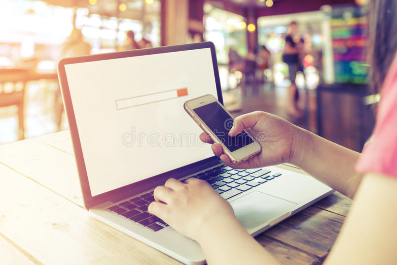 härlig ung hipsterkvinna` s räcker upptaget arbete på hennes bärbar dator, kvinnlign som använder sammanträde för celltelefon på  arkivfoton
