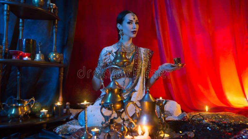 Härlig ung indisk kvinna i traditionella sarikläder med hällande te för orientaliska smycken in i koppen Indisk brud med festligt fotografering för bildbyråer