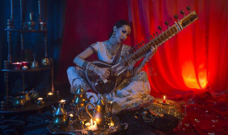 Härlig ung indisk kvinna i traditionella sarikläder med orientaliska smycken som spelar sitaren royaltyfria bilder