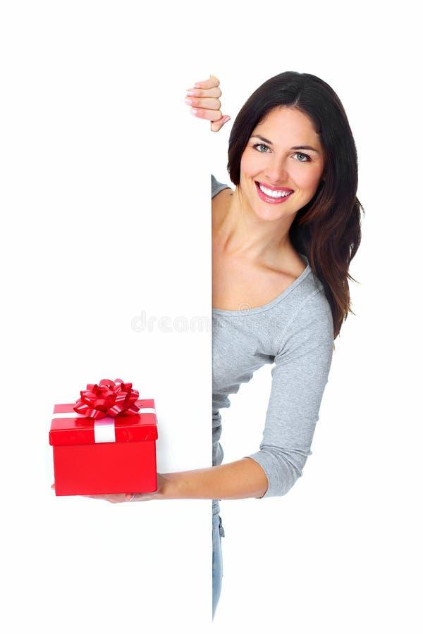 Härlig ung julflicka med en gåva. arkivfoton