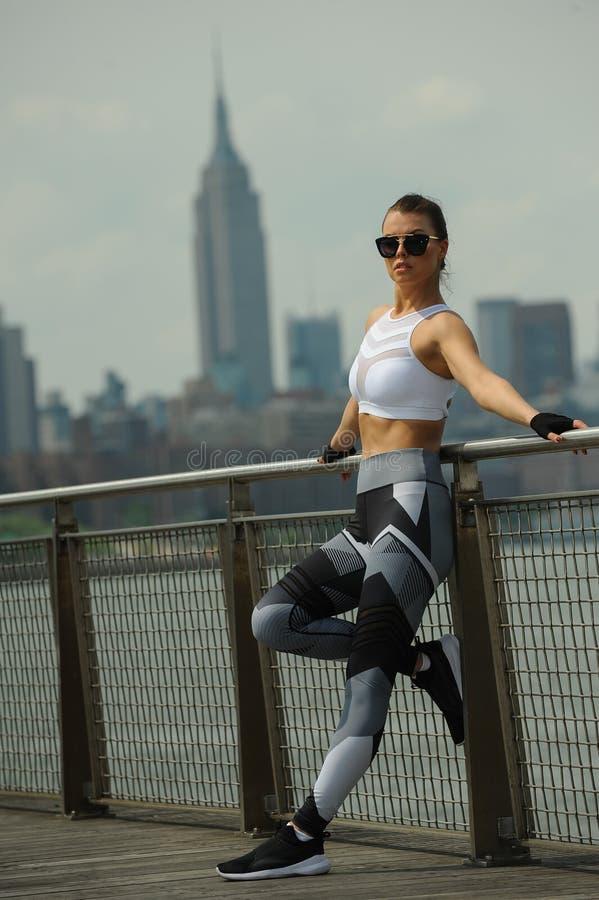 Härlig ung konditionmodell som bär den stilfulla sportswearen som poserar på pir royaltyfri fotografi