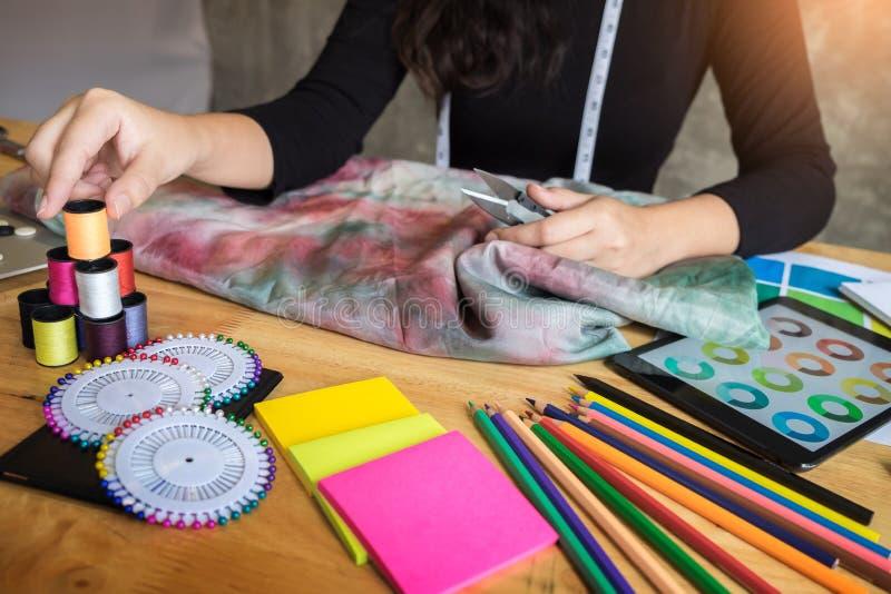 Härlig ung kvinna för modeformgivare som väljer tråden för sewin arkivbilder