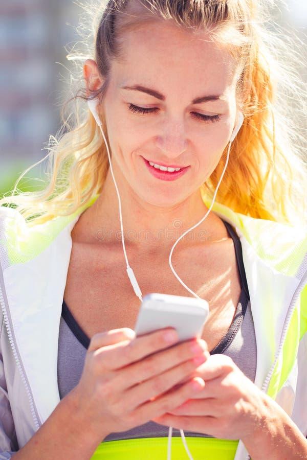 Härlig ung kvinna för stående med telefonen i hörlurar Sport på fotografering för bildbyråer