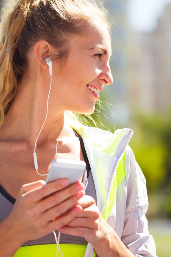 Härlig ung kvinna för stående med telefonen i hörlurar Sport på arkivbild