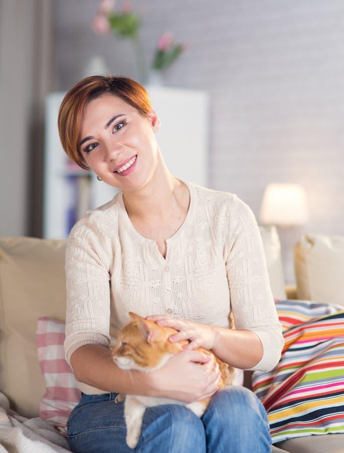 Härlig ung kvinna hemma på soffan med ett husdjur arkivbilder