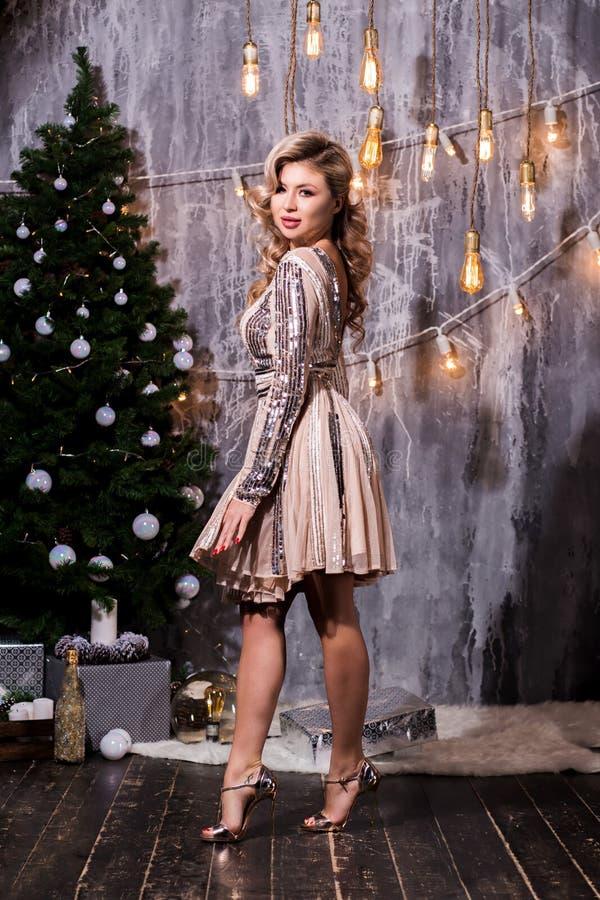 Härlig ung kvinna i anseende för elegant klänning bredvid julträd och gåvor royaltyfria bilder