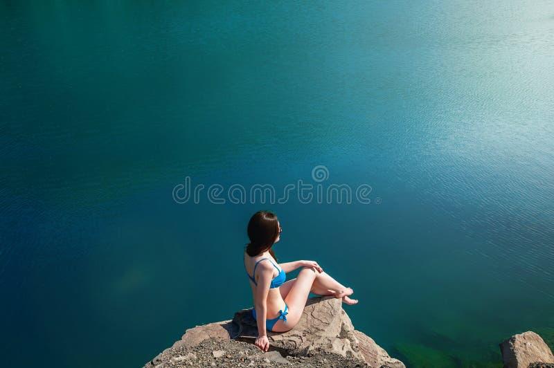 Härlig ung kvinna i baddräktanseende på sjön i morgonen Begreppsturism Blåtthav, Sky & moln royaltyfri fotografi