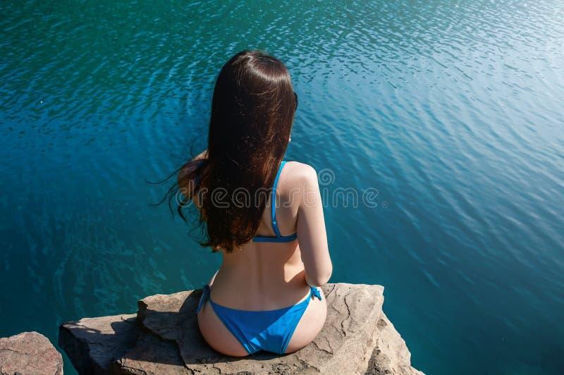 Härlig ung kvinna i baddräktanseende på sjön i morgonen Begreppsturism Blåtthav, Sky & moln arkivfoton