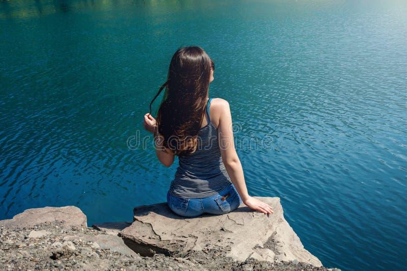 Härlig ung kvinna i baddräktanseende på sjön i morgonen Begreppsturism Blåtthav, Sky & moln fotografering för bildbyråer