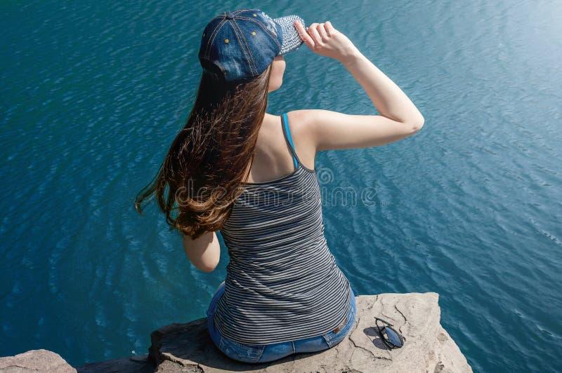 Härlig ung kvinna i baddräktanseende på sjön i morgonen Begreppsturism Blåtthav, Sky & moln royaltyfri foto