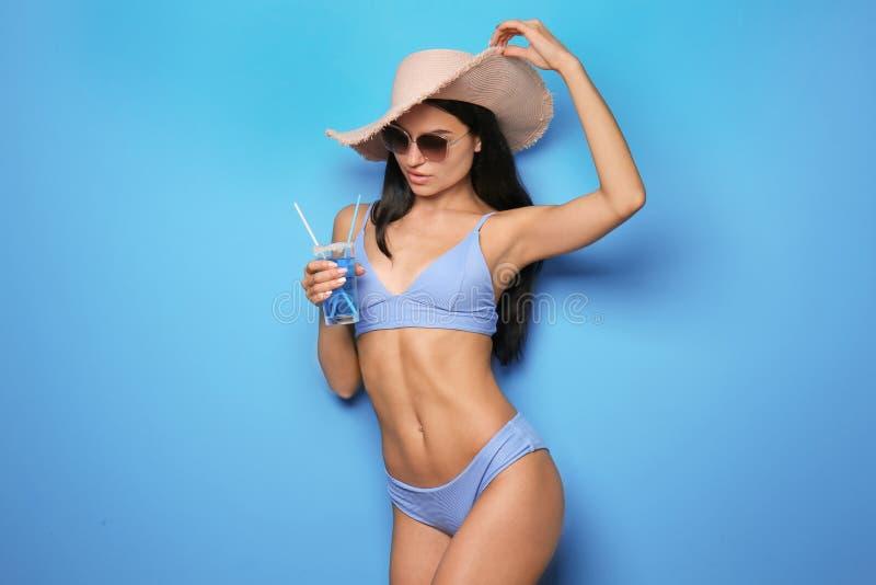 Härlig ung kvinna i bikini och med drinken på färgbakgrund royaltyfri fotografi