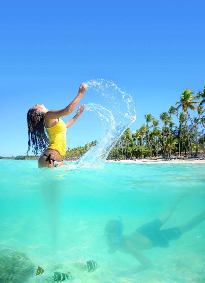 Härlig ung kvinna i bikini på den verkliga soliga tropiska stranden arkivbild