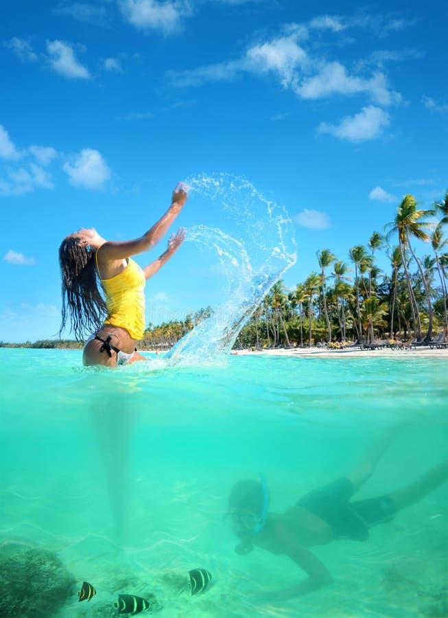 Härlig ung kvinna i bikini på den verkliga soliga tropiska stranden royaltyfri bild