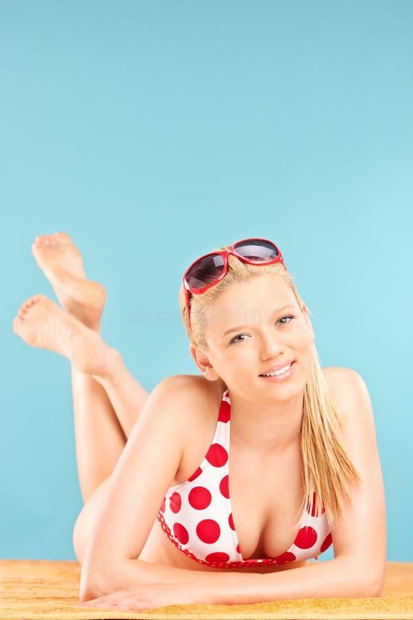 Härlig ung kvinna i bikinin som ligger på en strand royaltyfri bild