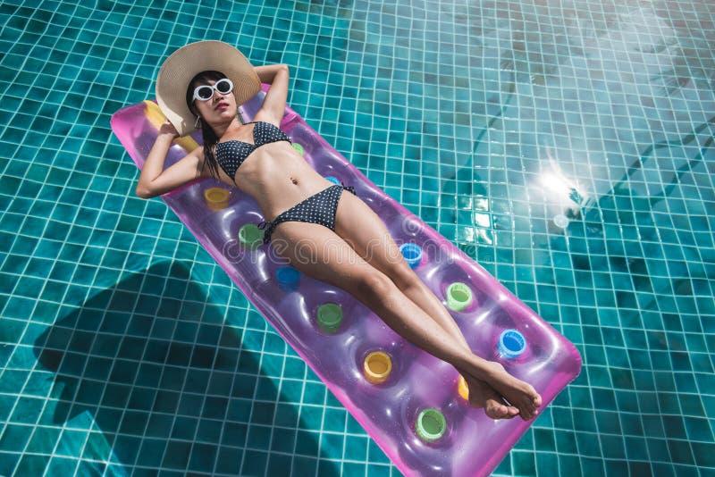 Härlig ung kvinna i bikinisimbassäng på madrassinflat royaltyfri foto