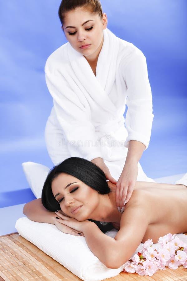 Härlig ung kvinna i brunnsortsalongen som tillbaka får massage, på blått arkivbilder