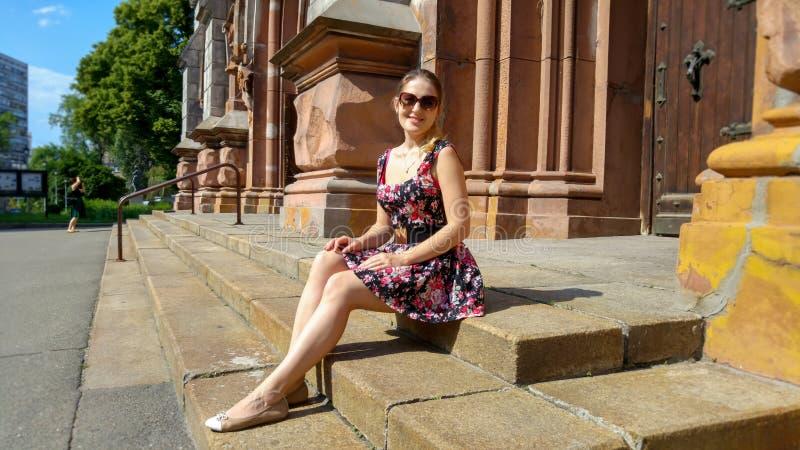 Härlig ung kvinna i den korta klänningen som sitter på gammal stentrappa på gatan av staden royaltyfri foto