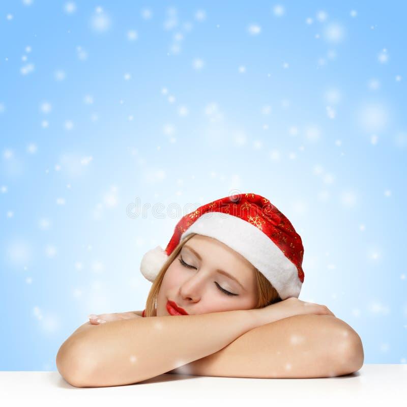 Härlig ung kvinna i den Santa Claus hatten som sover på tabellen arkivbild