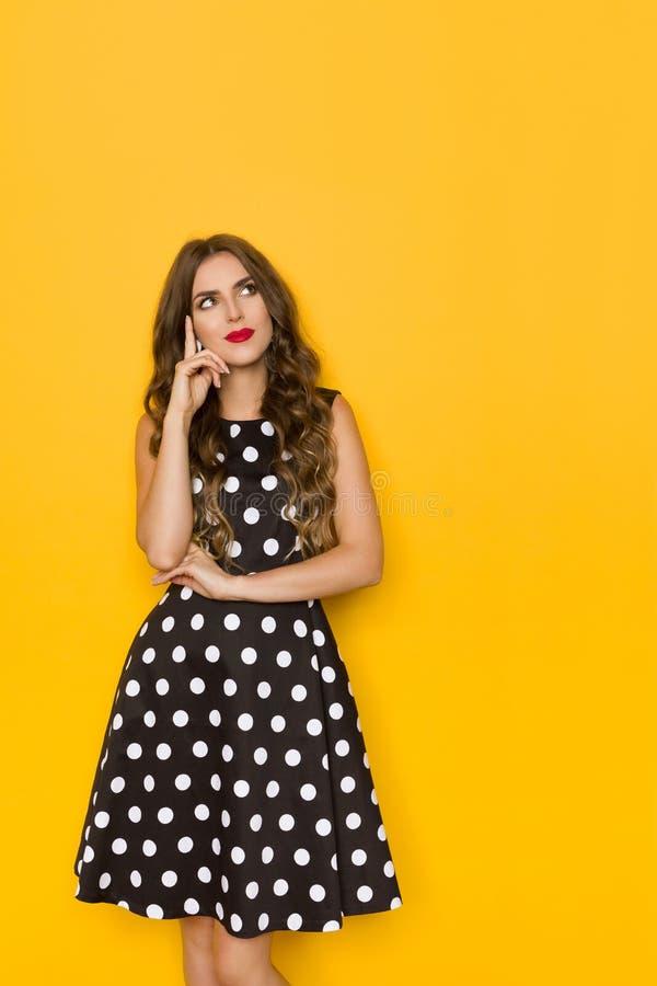 Härlig ung kvinna i den svarta Coctail klänningen, i polkaDots Is Looking Away And att tänka arkivfoto