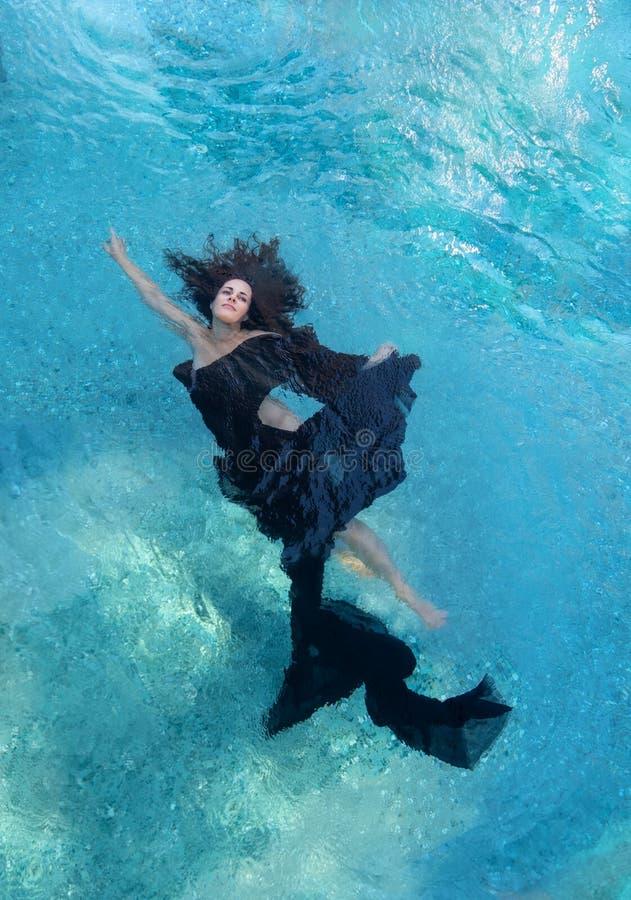 Härlig ung kvinna i den svarta klänningen, sväva för lockigt hår för mörk brunt som är solfjäderformigt i turkosvatten royaltyfri foto