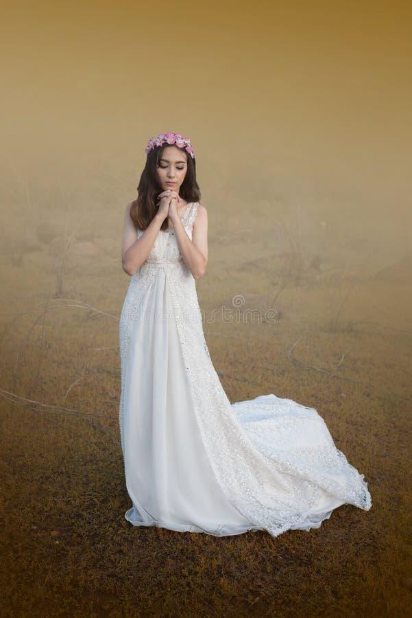 Härlig ung kvinna i den vita klänningen med blomman på hennes hår ut arkivfoton