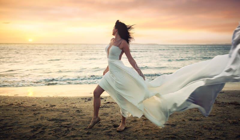 Härlig ung kvinna i den vita klänningen på en stormig strand arkivbilder