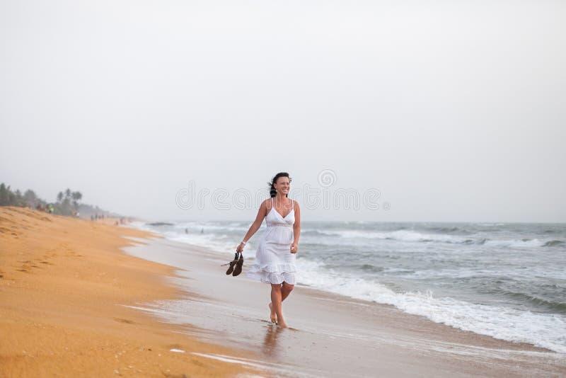 Härlig ung kvinna i den vita klänningen som går på den sandiga stranden som rymmer sandaler Lopp- och sommarbegrepp royaltyfri bild
