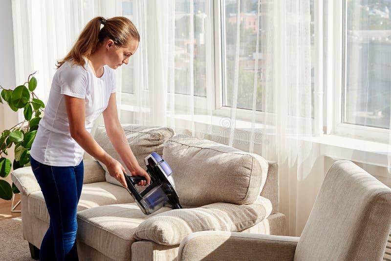 Härlig ung kvinna i den vita skjortan och jeans som gör ren soffan med dammsugare i vardagsrum, kopieringsutrymme hush?llsarbete royaltyfri bild