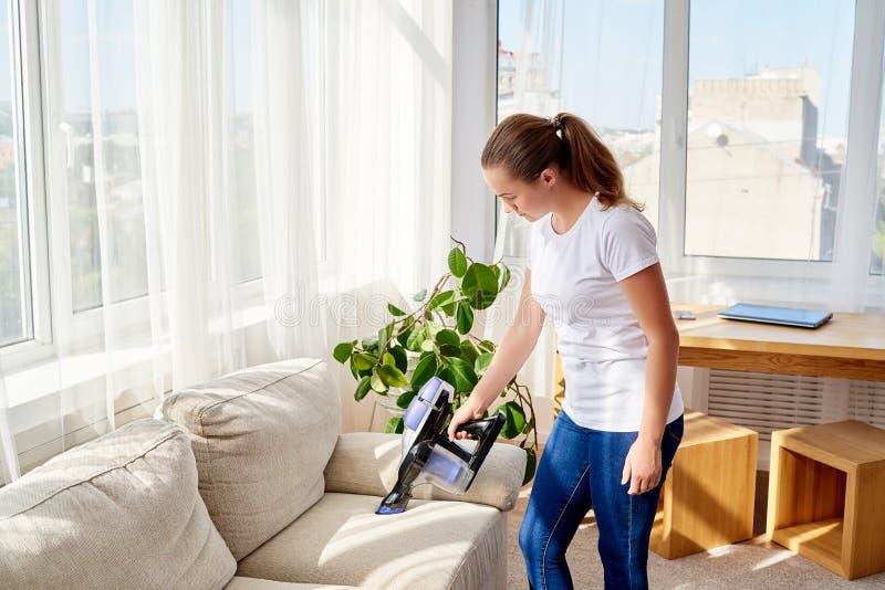 Härlig ung kvinna i den vita skjortan och jeans som gör ren soffan med dammsugare i vardagsrum, kopieringsutrymme hush?llsarbete royaltyfri fotografi