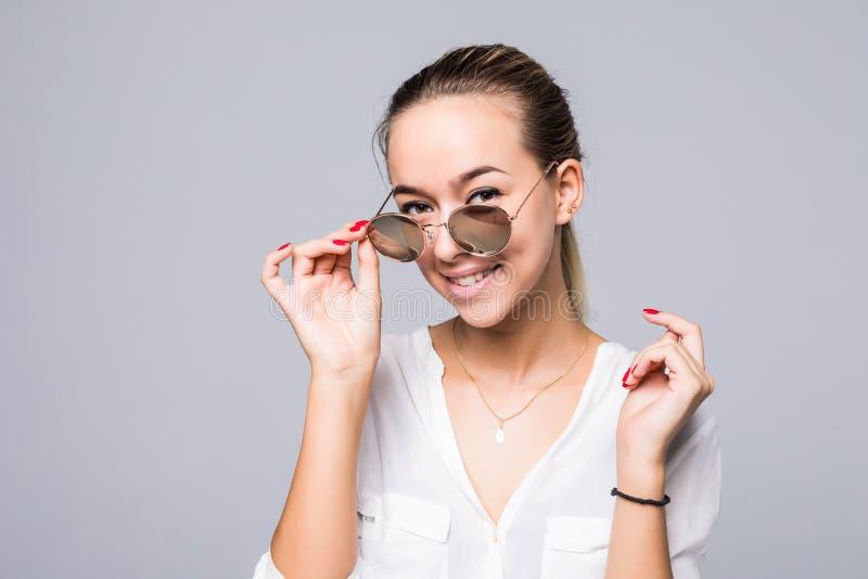 Härlig ung kvinna i elegant solglasögon som ler över grå bakgrund royaltyfri fotografi